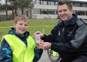 Verkehrsinstruktor Stefan Hinrikson übergibt den Preis an den Gewinner Sascha Koradi, der in Oberneunforn die sechste Primarschulklasse besucht. (Bild: Kapo TG)
