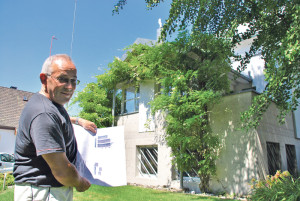 Peter Schreck mit einem Plan des Bauprojekts vor seinem Haus, das er für den Neubau abreissen lassen will. (Bild: Thomas Martens)