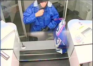 Bildlegende: Das Bild zeigt den Täter mit auffällig blauer Jacke am Bankschalter. (Bild: Kapo TG)