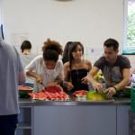 Jugendliche schneiden Melonen auf fürs Abendessen. Maeva Quilgard (Frankreich), Coline Saib (Frankreich), Mihai Ungur (Rumänien). (Bild: Silas Wuttke)