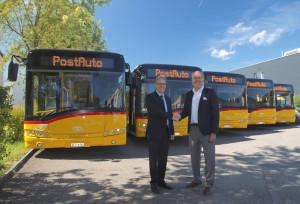 Hans Thommen (re.) von der Solaris Schweiz GmbH übergibt Walter Schwizer, Leiter PostAuto-Region Ostschweiz, die fünf neuen Postautos. (Bild: PostAuto Schweiz AG)