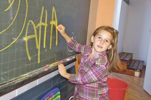 Szenen aus demFlüchtlingscafé: Die kleine Ana Stevic malt an der Tafel im Kinderspielzimmer.