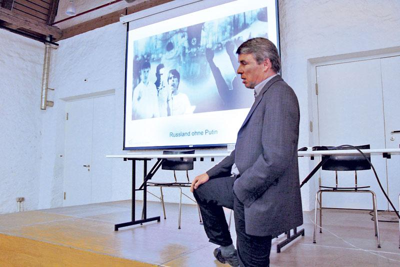 Prof. Dr. Ulrich Schmid beim VHS Vortrag über Russlands Politik. Im Hintergrund läuft ein Propagandavideo, das aufzeigt, wie Russland ohne Putin im Choas versinken würde.(Bild: ek)
