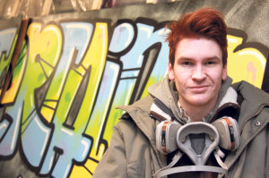 Reto «rways» Ritz in Arbeitsmontur vor einem frisch gesprayten Graffiti. (Bild: ek)