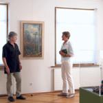 Ausstellungsgestalter Philippe Mahler und Museumsleiterin Heidi Hofstetter betrachten eine Landschaft von Johannes Diem. (Bild: ek)