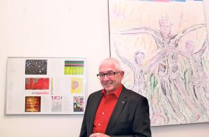 Aurelio Wettstein vor einem seiner Gemälde samt Erklärungen dazu. (Bild: ek)