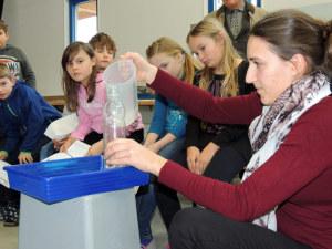 Mit ihrer Lehrerin Maria Barmettler führen Steckborner Schüler ein Experiment zum Thema Wasserdruck durch. (Bild: zvg)
