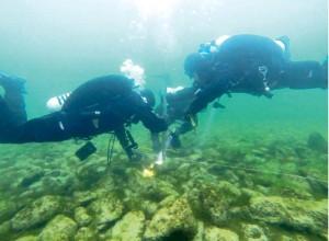 Forschungstaucher untersuchen einen der Steinhaufen. (Bild: zvg)