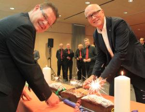 Schulpräsident René Zweifel und Stadtpräsident Andreas Netzle (v.l.) schneiden den zehn Meter langen Geburtstagskuchen gemeinsam an. Im Hintergrund sind Mitglieder des Männerchors Harmonie zu sehen, die den Festakt auf der Galerie musikalisch umrahmten. (Bild: IDK)